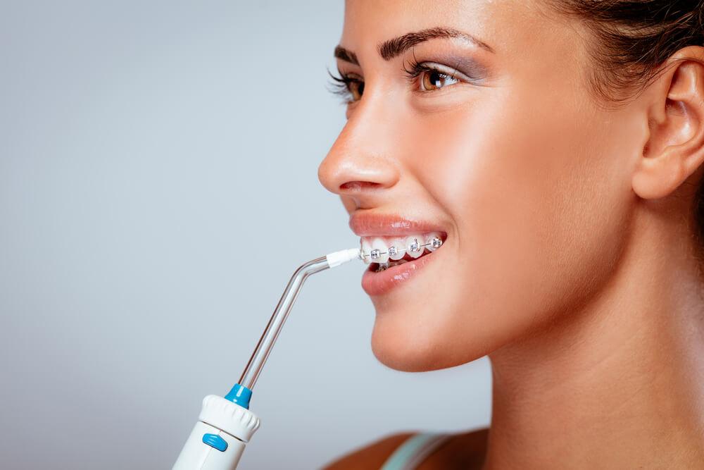 mujer con irrigador dental